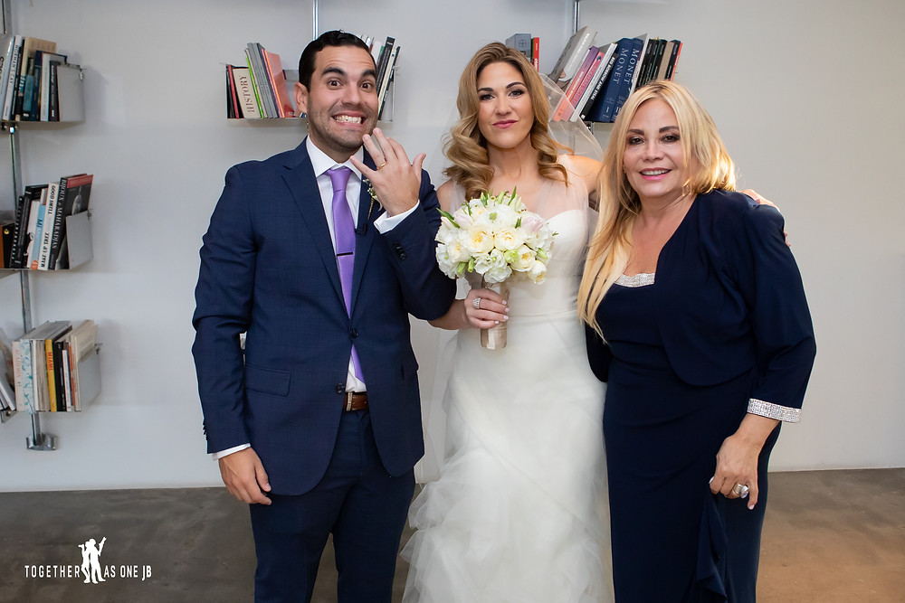 Groom showing ring with bride and groom's mother after ceremony at the M Building in Wynwood