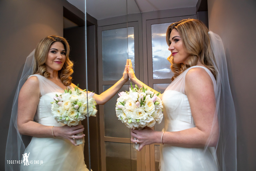 Bride posing with wedding flowers in front of mirror in the M Building in Wynwood