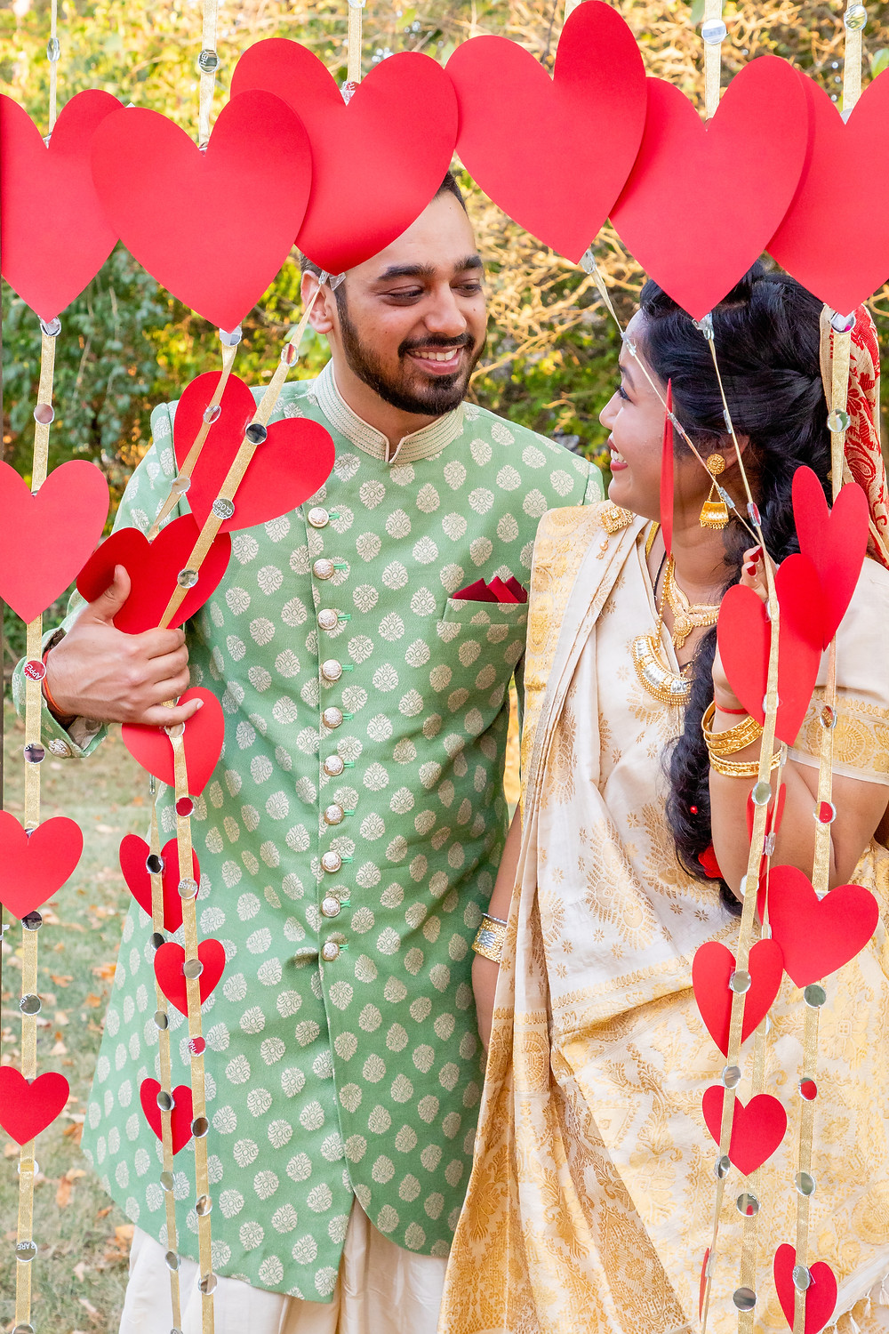Indian wedding photographer captures image of indian husband and wife smiling at each other with heart decorations.