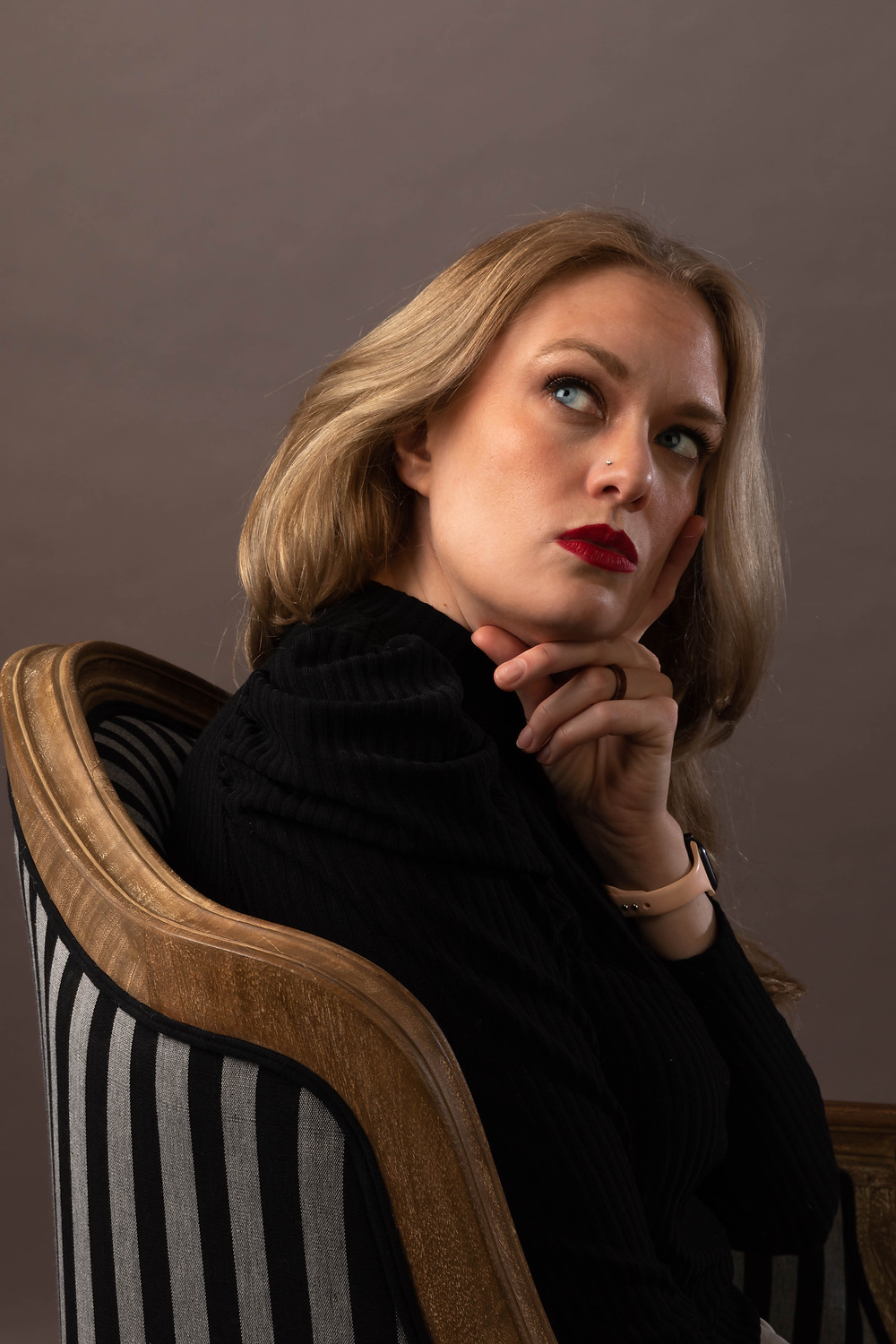 Cincinnati portrait photographer captures image of woman looking upwards on side profile sitting in a chair.