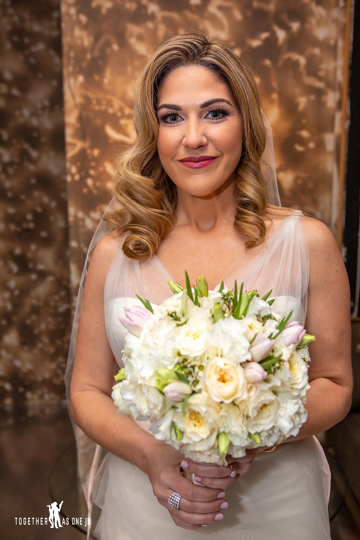 Bride posing with wedding flowers in bridal suite in the M Building in Wynwood