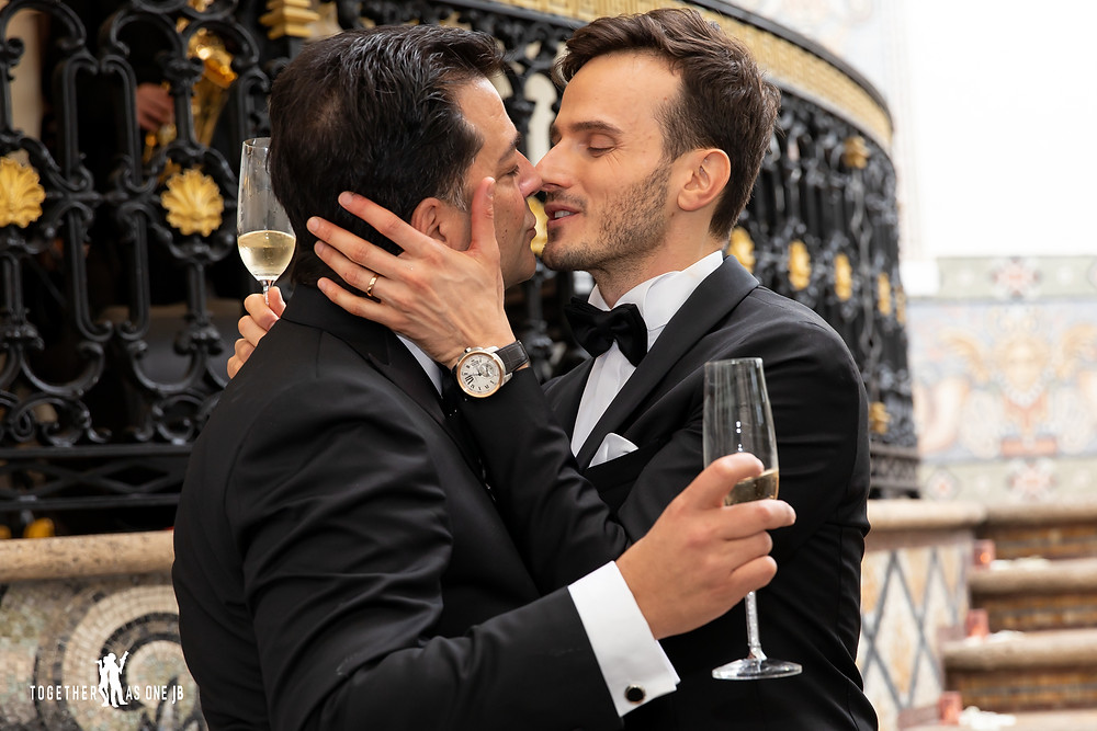 Grooms sharing a kiss after drinking glass of champagne