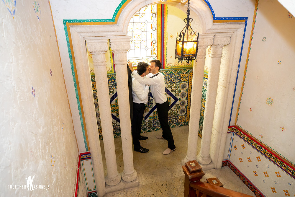 Grooms kissing at the bottom of stairs in front of stained glass windows
