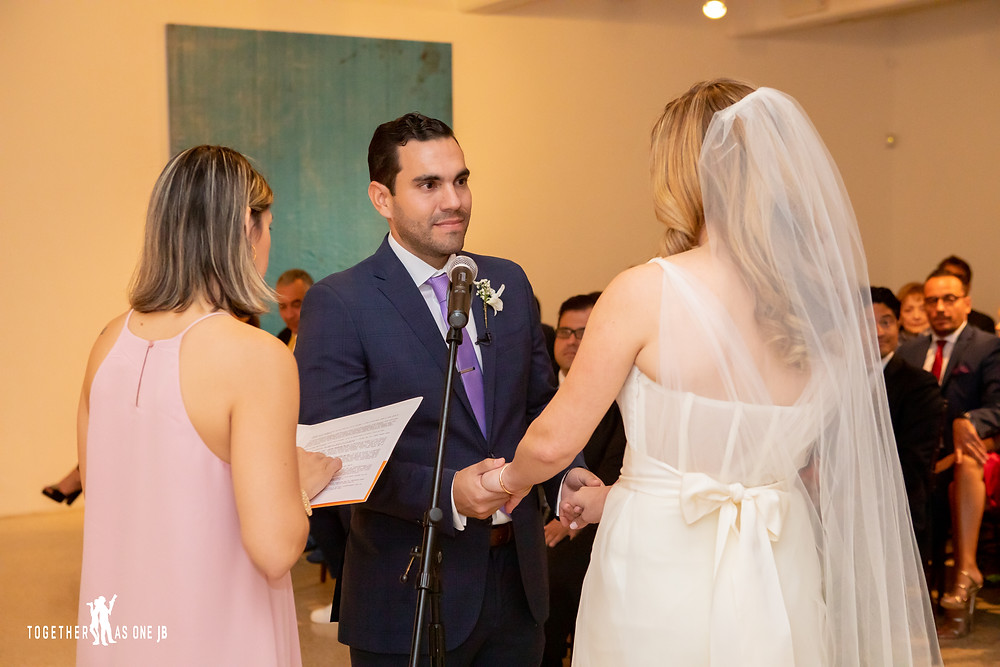 Groom looks at bride during wedding ceremony at the M Building in Wynwood