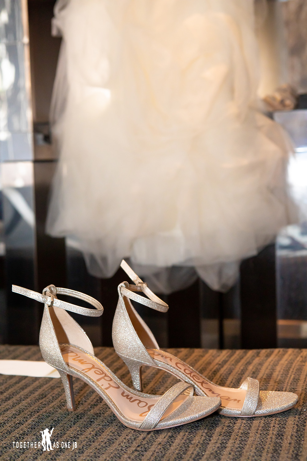 Close up of shoes with wedding dress in background in bridal suite