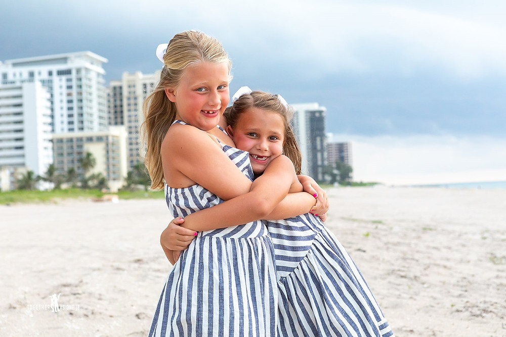 Cincinnati wedding photographer captures image of sisters wearing matching outfits in the beach hugging each other.