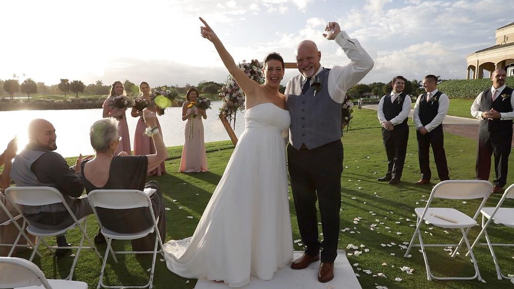 Cincinnati wedding photographer captures image of married couple cheering outdoors just married.