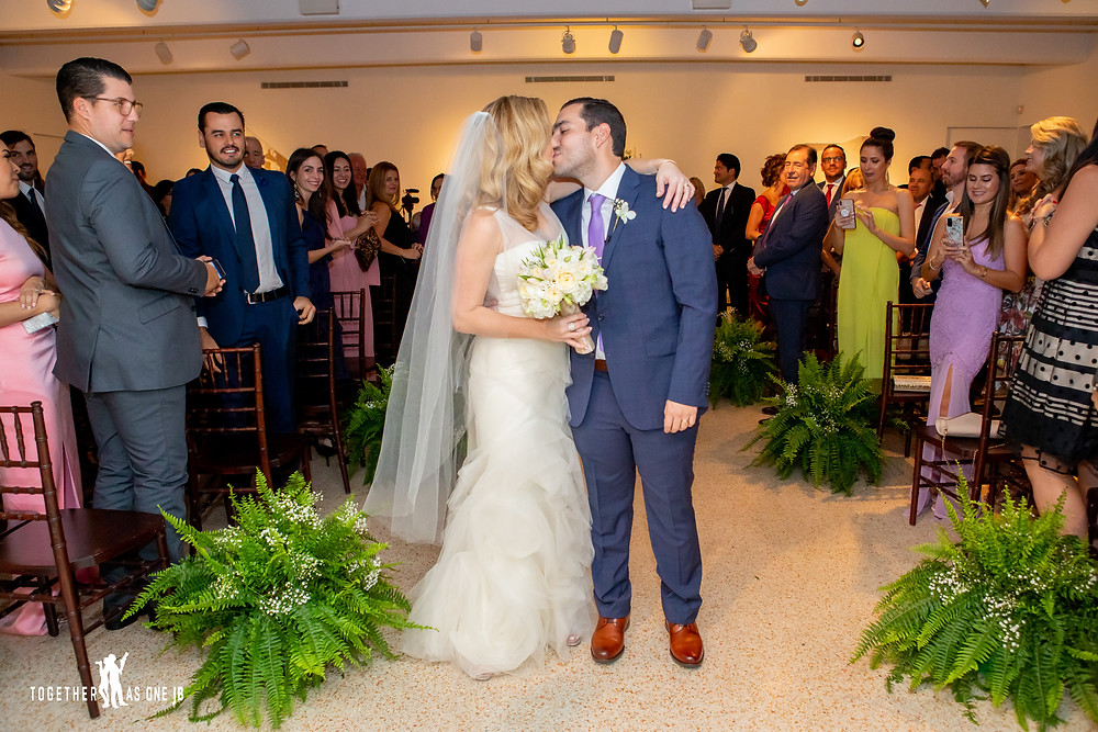 Bride and Groom kissing at the end of aisle after wedding ceremony at the M Building in Wynwood