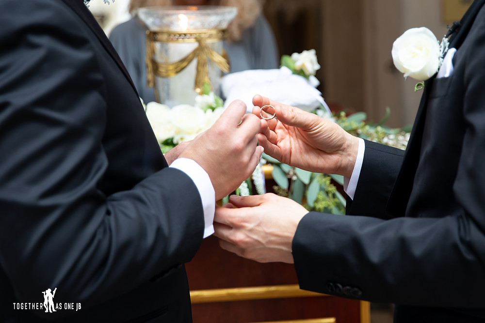 Close up of wedding band and grooms hands