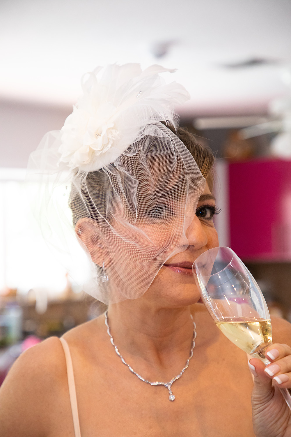Miami wedding photographer captures image of bride with veil drinking from a fancy glass.