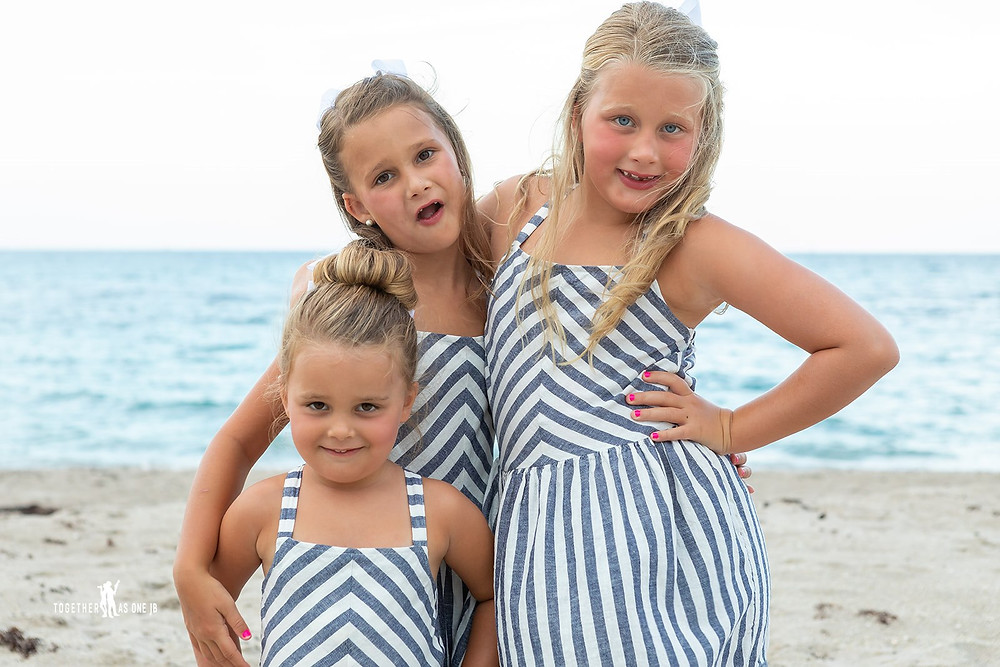 Cincinnati wedding photographer captures image of three little girls wearing matching outfits posing for a picture in the beach.