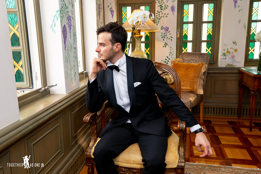 groom looks out window of the former Versace Mansion