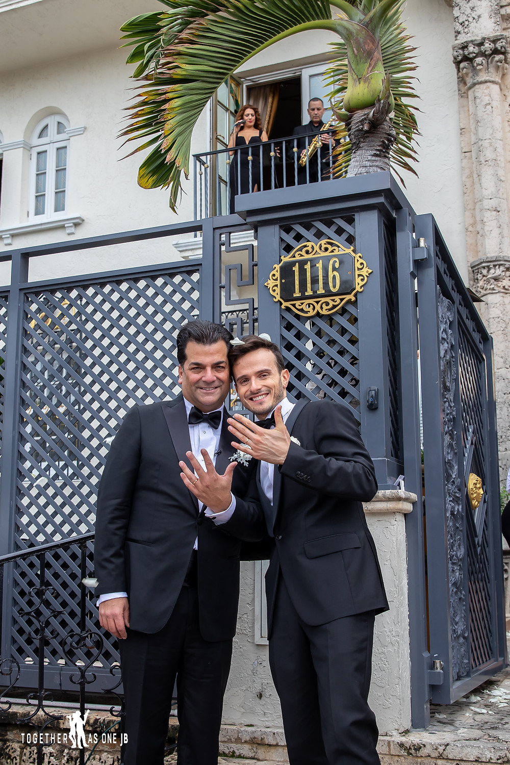 Grooms show wedding bands in front of Villa Casa Casuarina while singer and saxophone player play music