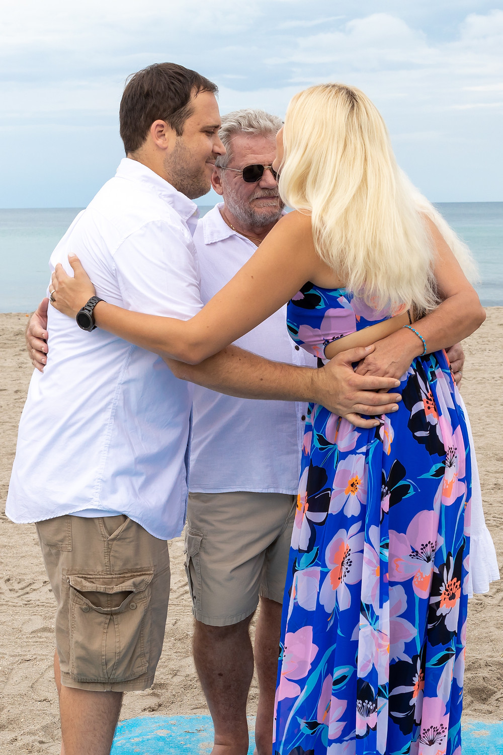 Cincinnati wedding photographer captures image of husband and wife hugging with a friend on the beach.