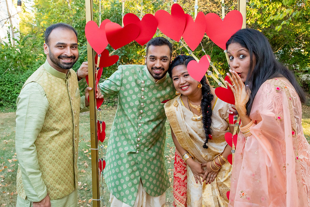 Indian wedding photographer captures image of indian family smiling under heart decortations.