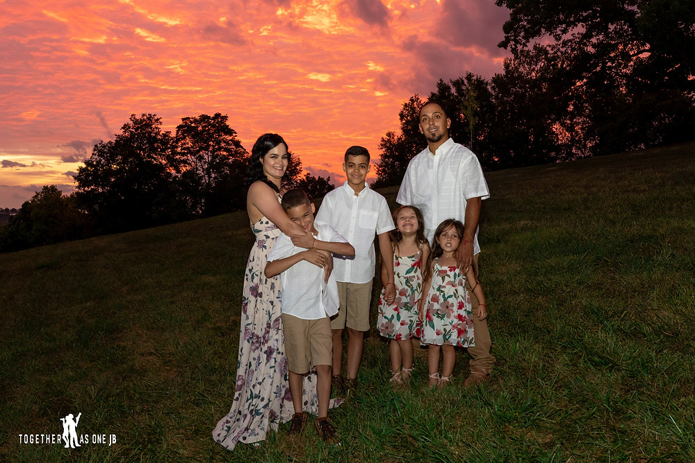 Family Sunset photography of orange sky in Mount Snow Cincinnati Ohio.  This beautiful family is having one of their most entertaining moments during their family portrait session by Together As One JB.