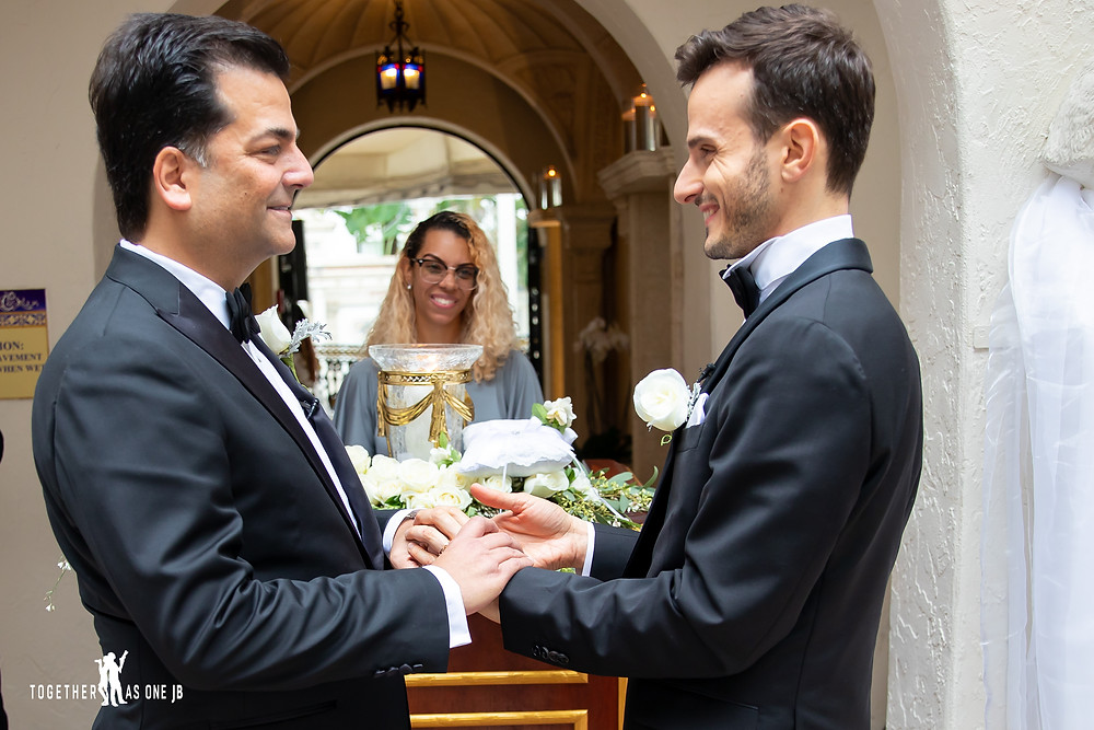 Grooms look lovingly into each other eyes as wedding officiant looks at them
