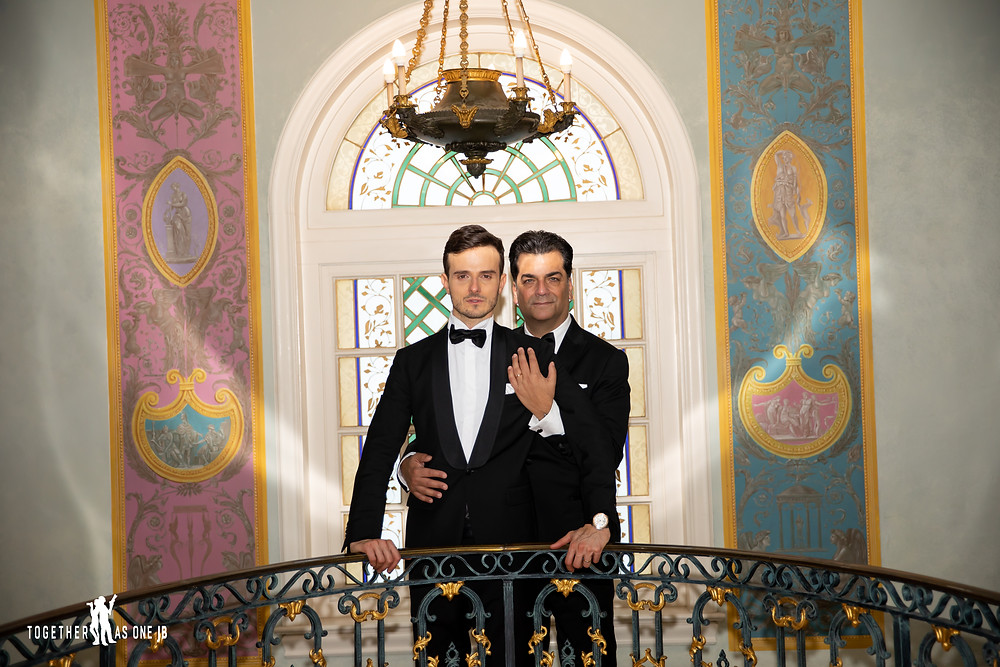 Grooms embracing each other with light reflecting on their faces