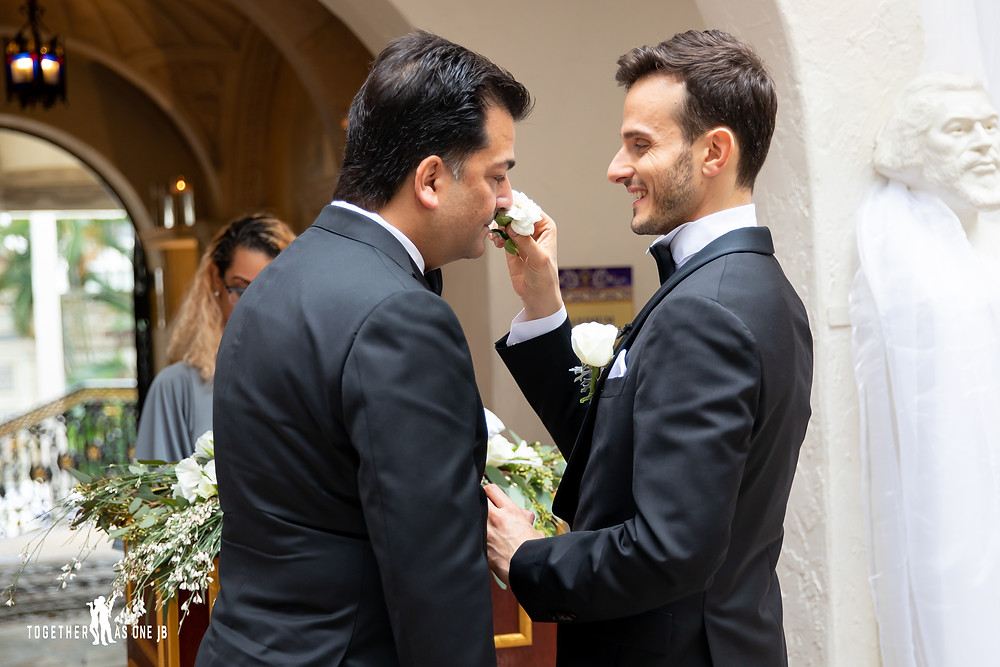 Groom holds flower to groom to smell during wedding ceremony