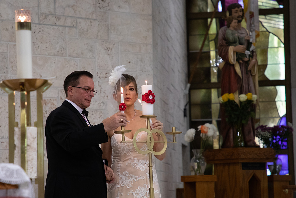 Miami wedding photographer captures image of husband and wife holding candles in church.