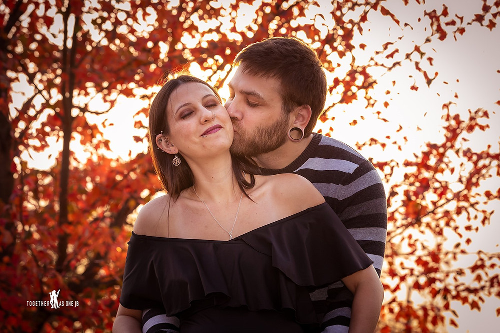 Cincinnati wedding photographer captures photograph of man kissing cheek of smiling woman in sunset in the woods.