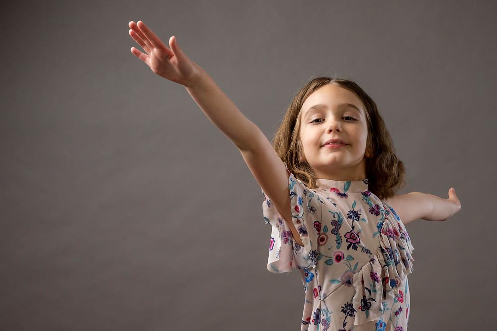 Cincinnati portrait photographer captures girl with hands up smiling.