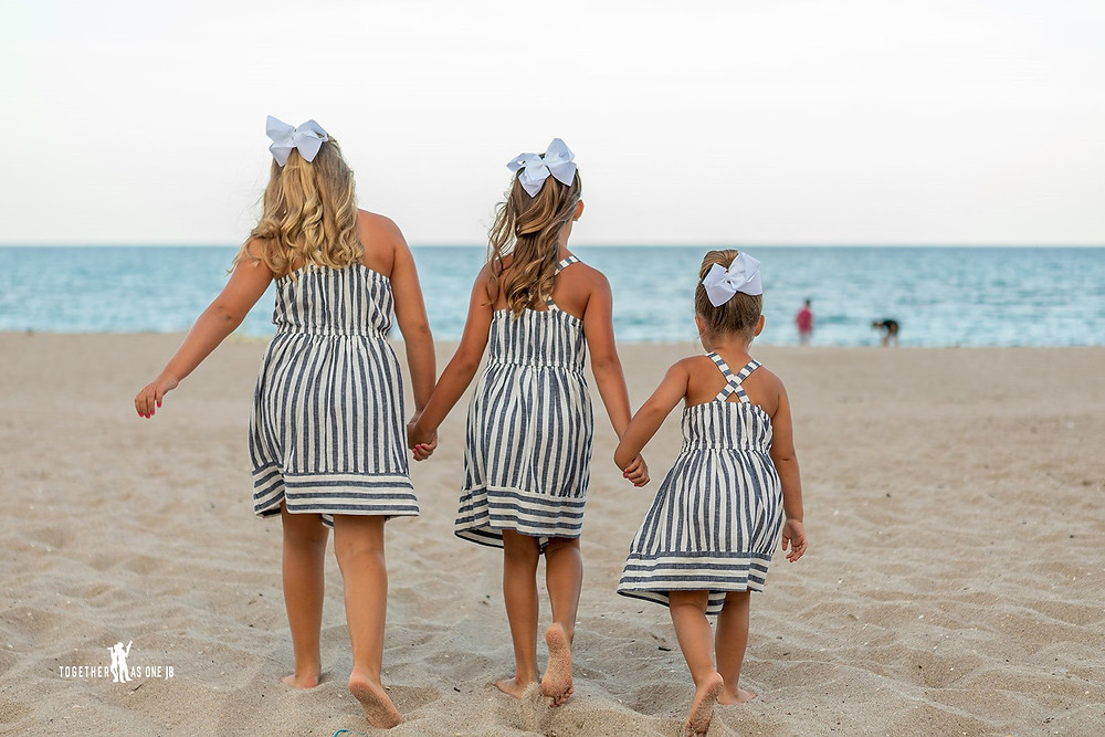 Cincinnati wedding photographer captures image of three little girls wearing matching outfits in the beach.