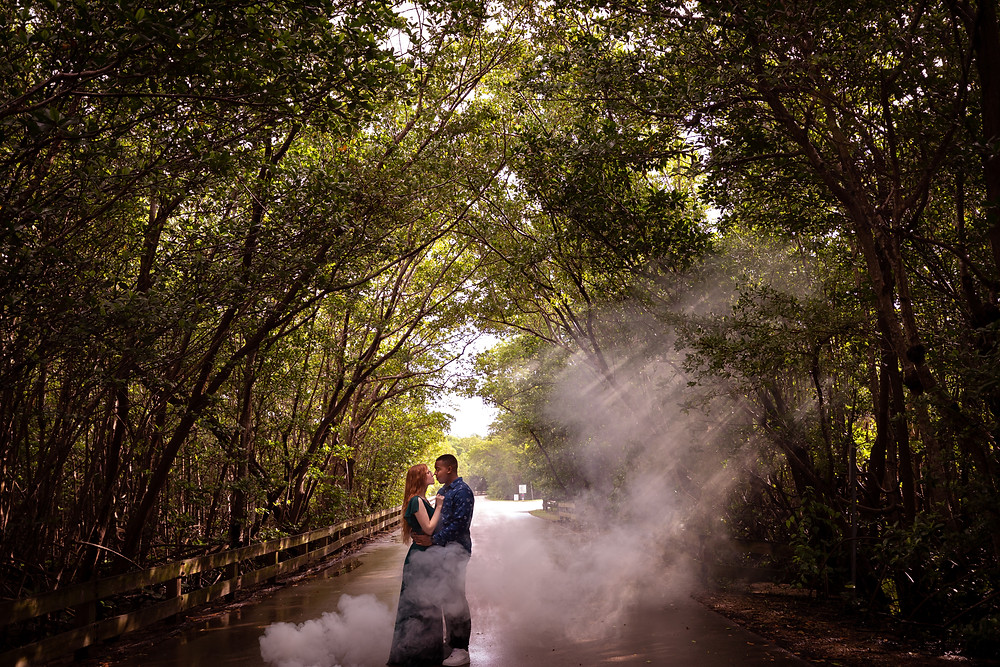 Miami wedding photographer captures image of couple kissing under trees in smoke in the forest.