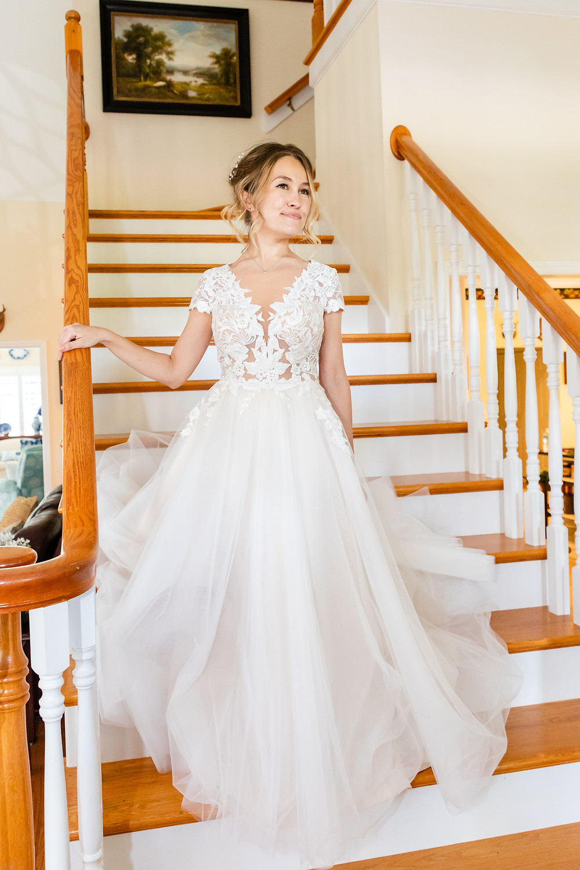 Cincinnatti wedding photographer captures image of bride going down the stairs wearing her wedding dress.