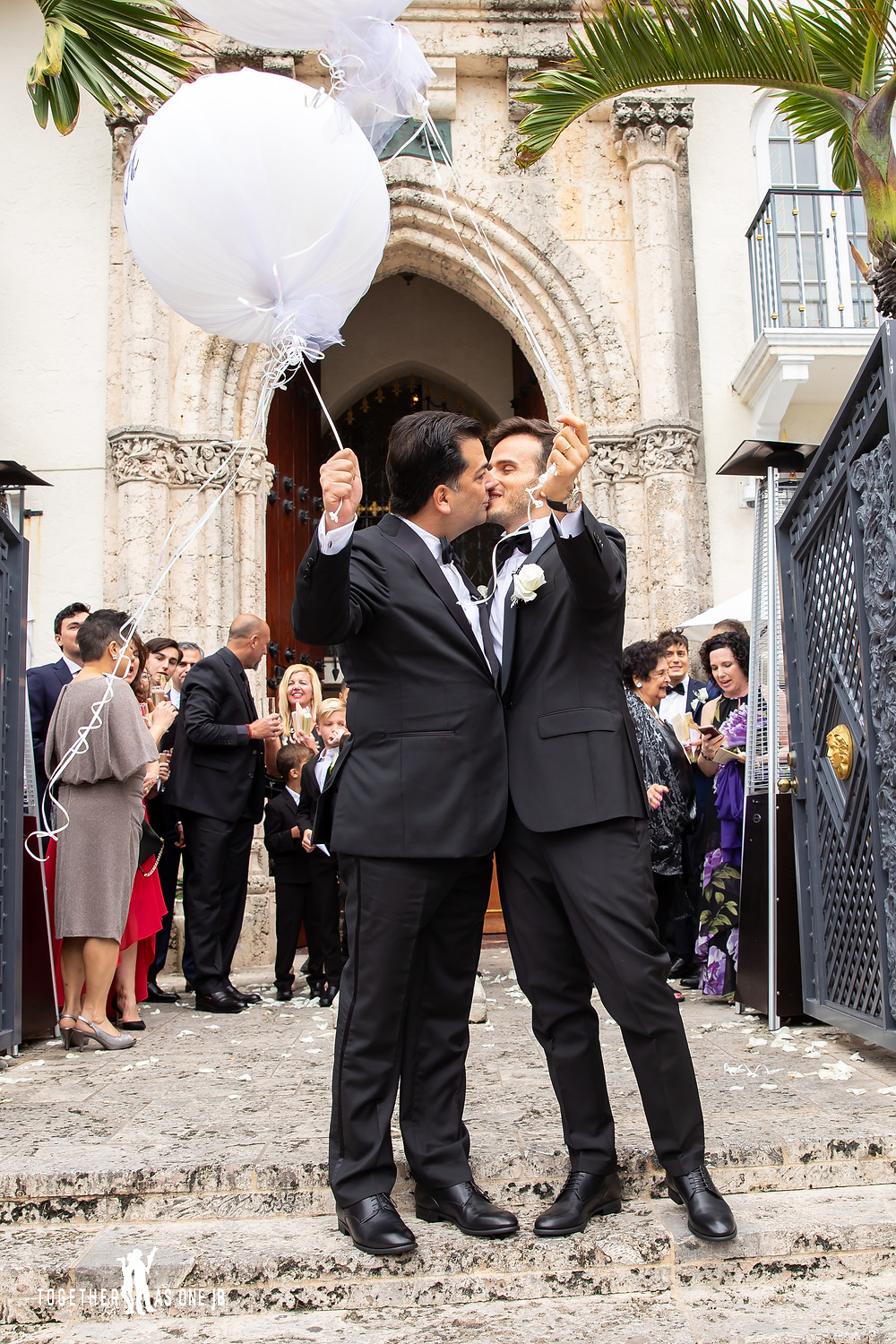 Grooms kiss as wedding guest enjoy cocktail hour groom hold wedding balloons