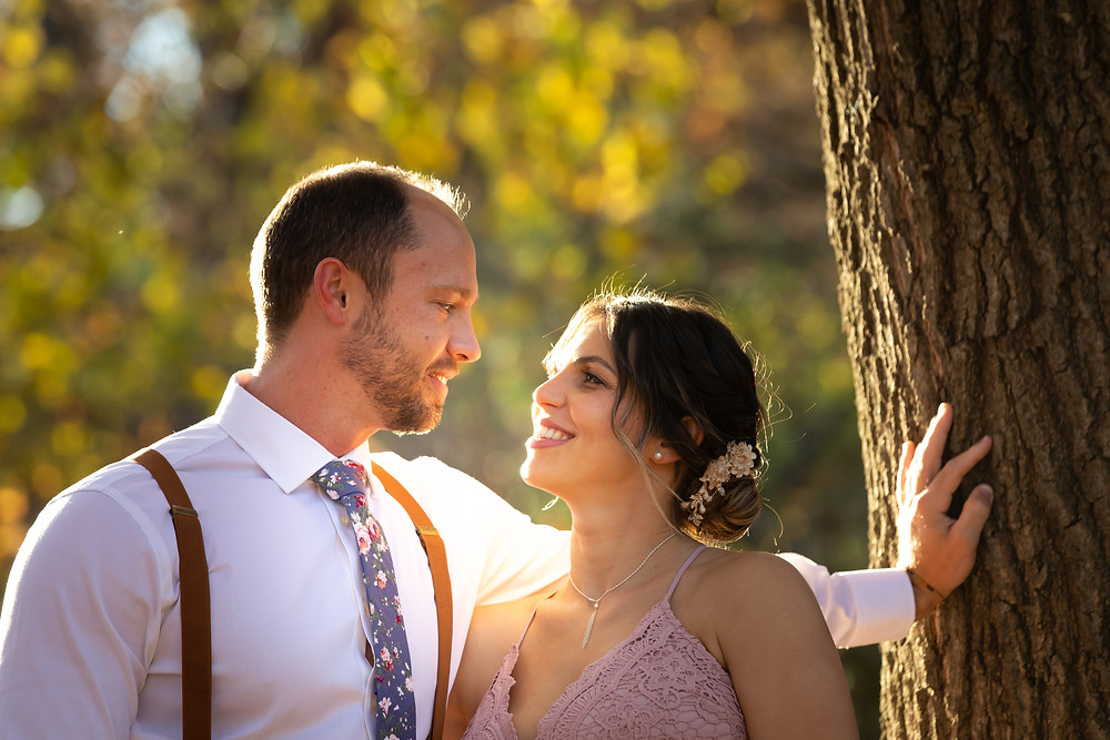 Cincinnati wedding photographer captures image of groom leaning on tree smiling at bride.
