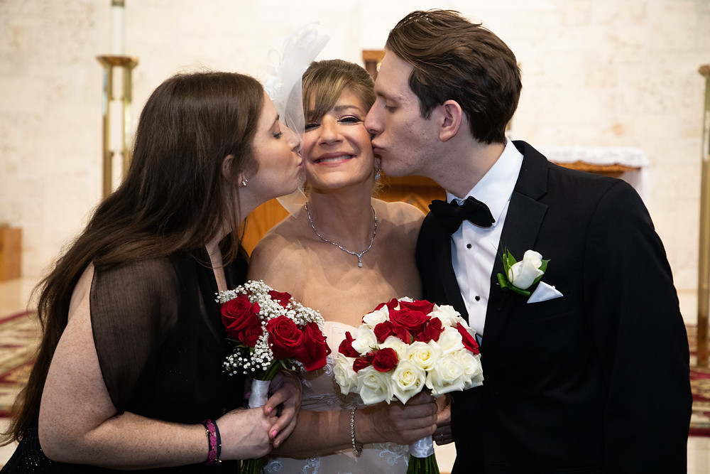 Miami wedding photographer captures image of bride being kisses in each cheek by family members holding a bouquet of flowers.