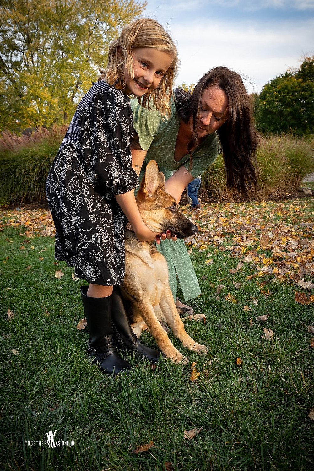Cincinnati family photographer captures photography of family playing with dog in yard.