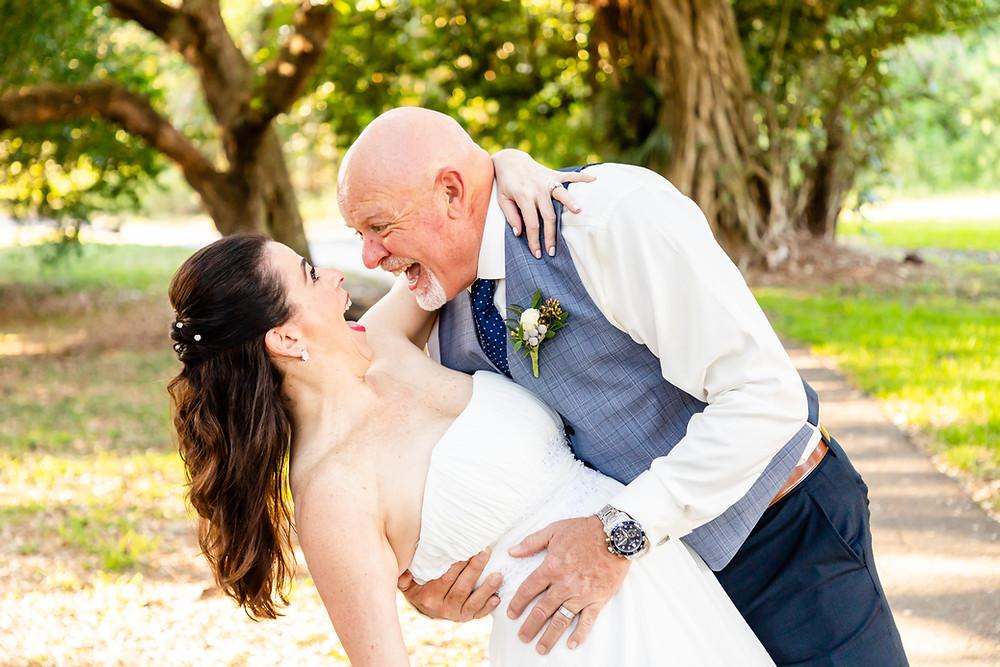 Cincinnati wedding photographer captures image of husband dipping wife smiling in park.