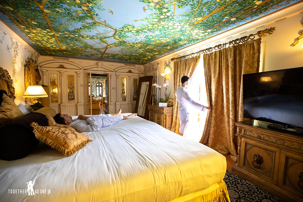 Groom looks out window while other groom lays on king sized bed in guest bedroom of the former Versace Mansion