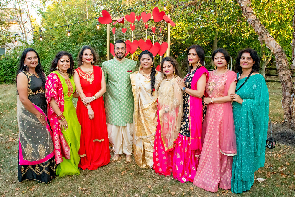 Indian wedding photographer captures image of indian family smiling together for a picture outside.
