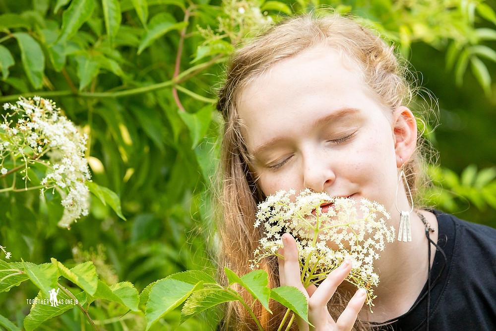 Cincinnati family photographer captures portrait of smiling girl smelling white flower closing her eyes.