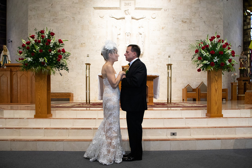 Miami wedding photographer captures image of husband and wife at the altar in a church.