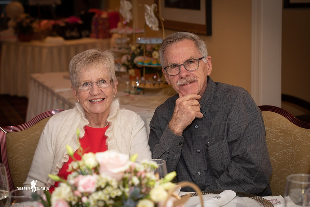 Cincinnati family photographer captures image of elder couple smiling posing for picture at fancy table.