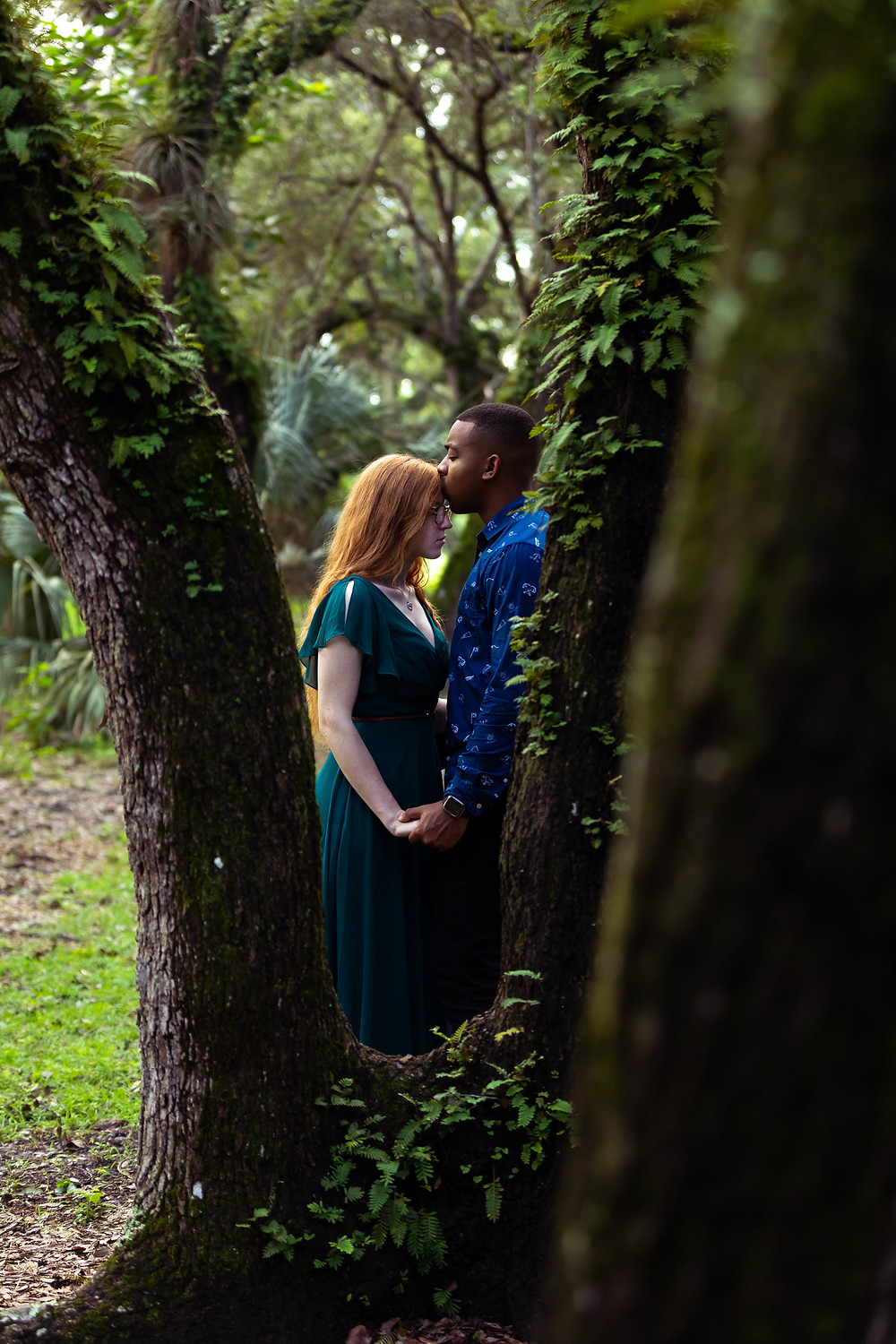 Miami wedding photographer captures image of husband kissing forehead of wife behind a tree in the forest.