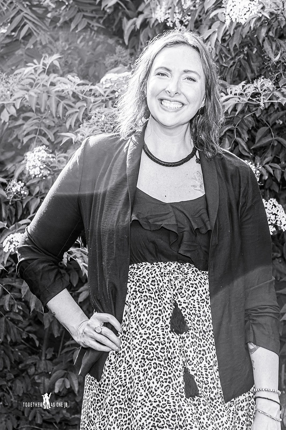 Cincinnati family photographer captures black and white portrait of smiling woman in yard.