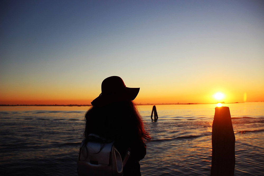 A girl observing the sunset in Burano