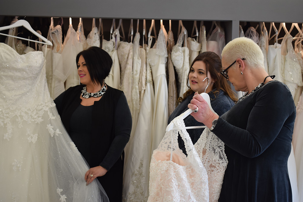 Left to right: Alison, Pippa and Jo alongside the many bridal gowns Curve & Couture have to offer.