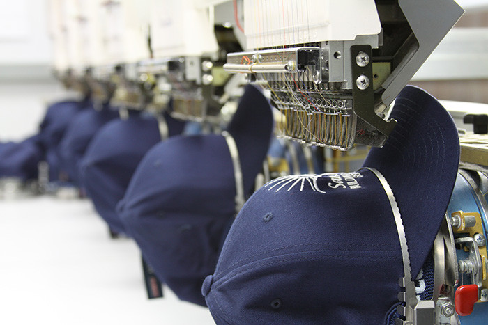 baseball caps being embroidered on a machine.