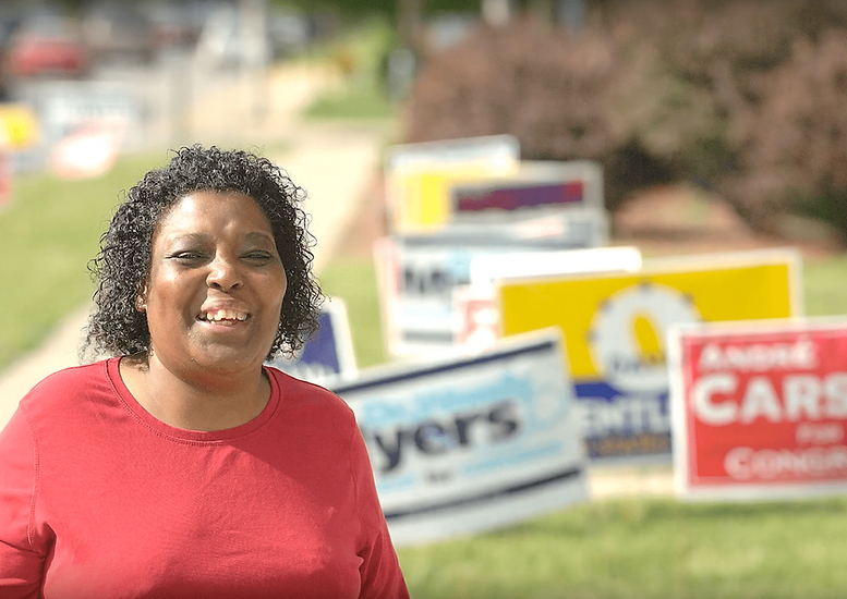Picture of late disability rights activist Betty Williams.  Betty is a Black woman wearing a red t-shirt and smiling broadly at the camera.  Behind her are several political campaign signs.