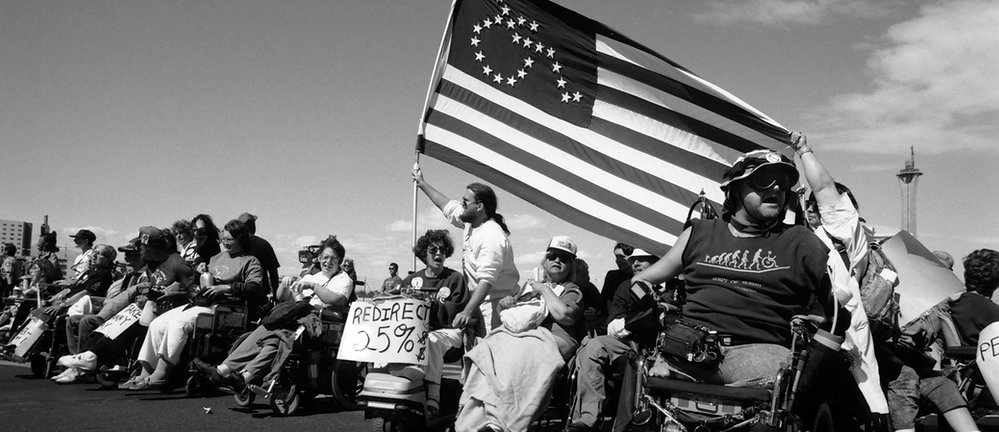 """Black and white photo of a line of disability rights activists.  Almost all are wheelchair users.  One holds a sign that says """"redirect 25%"""" and another is holding an American flag.  The flag has the stars arranged to form the shape of a wheelchair accessability symbol."""