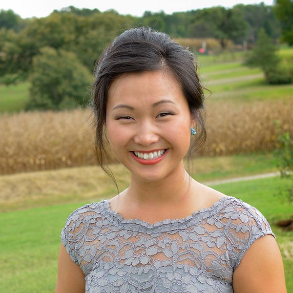 Photo of Katie Gullquist.  Katie is an Asian-American woman in her 20s with long black hair.  She is smiling widely in a semi-formal dress while standing in a country field.