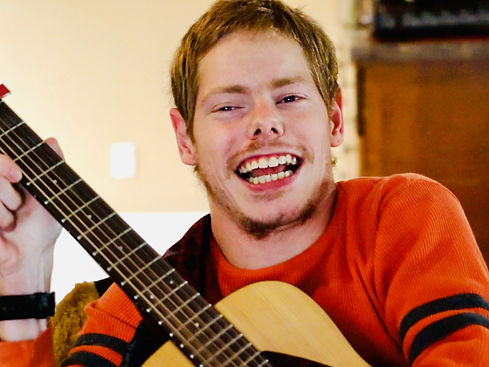 Caucasian man in his twenties with short reddish hair.  Smiling at the camera and holding a guitar.