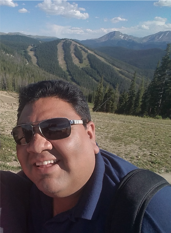 Photo of Josh Garcia.  Latinx male in his 30's with short black hair and sunglasses.  Josh is standing on a mountain top with several mountains behind him.