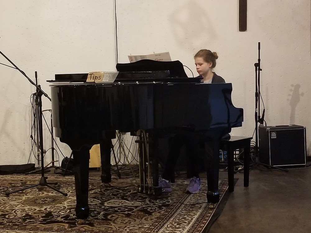 Girl playing grand piano at coffee shop with large area rug